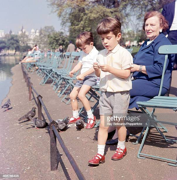 John F Kennedy Junior son of the late United States president and his cousin Anthony Radziwill feeding the pigeons in St James' Park while touring...