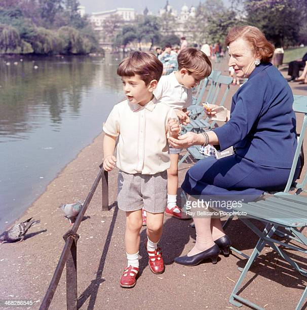 John F Kennedy Junior son of the late United States president and his cousin Anthony Radziwill feeding pigeons in St James' Park while touring London...