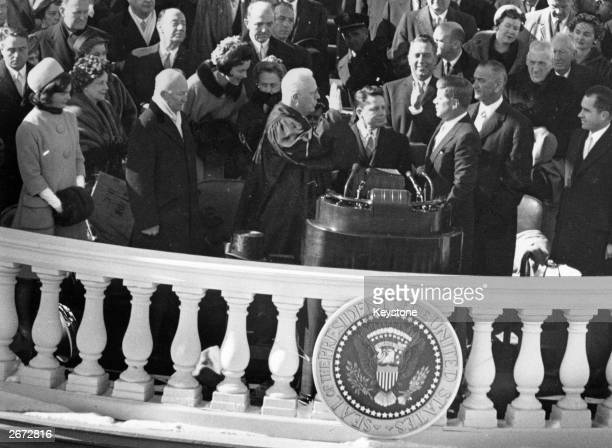 John F Kennedy taking the Oath of Office administered by Chief Justice Earl Warren . James Browning, Clerk of the Supreme Court, is centre and Jackie...