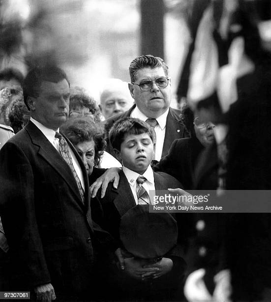 John Fahy Jr. Holds his father's police cap as he enters St. Thomas More Church in Breezy Point, Queens, for the funeral of his father, Deputy...