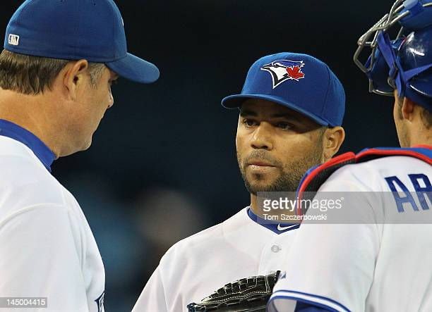 John Farrell of the Toronto Blue Jays talks to Luis Perez and JP Arencibia during MLB game action against the New York Mets on May 18 2012 at Rogers...