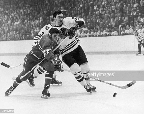 John Ferguson of the Montreal Canadiens battles for the puck with Cliff Koroll of the Chicago Blackhawks during a game circa 1971 at Chicago Stadium...