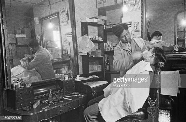 John Fernandes, a Portuguese barber born in Sao Vicente, Cape Verde, gives a customer a shave in his barbershop in Tiger Bay, a multicultural area of...