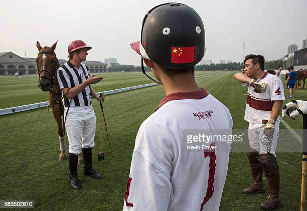John Fisher, Director of Stable Operations, left, speaks with Chinese players Quan Zehao, right, and Dai Zihan from the Metropolitan Polo Club team...