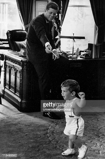 John Fitzgerald Kennedy , 35th President of the United States, serving from 1961 with his son at the White House.