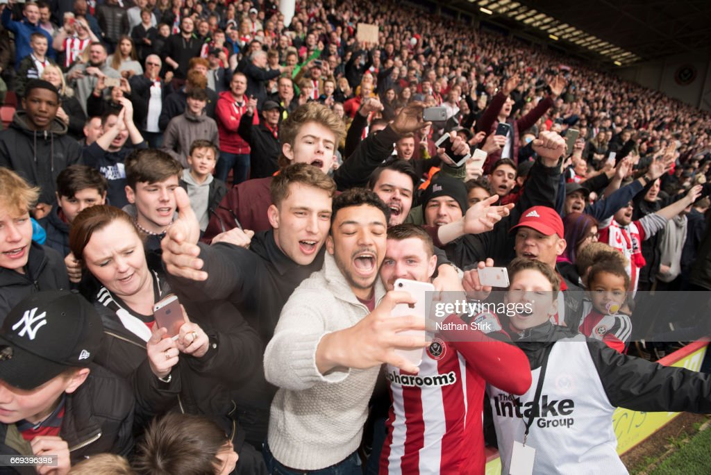 John Fleck of Sheffield United has a selfie with fans after winning promotion to the Sky Bet Championship after the Sky Bet League One match between Sheffield United and Bradford City at Bramall Lane on April 17, 2017 in Sheffield, England.
