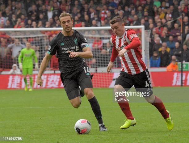 John Fleck on the attack monitored by Jordan Henderson at the English Premier League Match between Sheffield United and Liverpool at the Bramall Lane...
