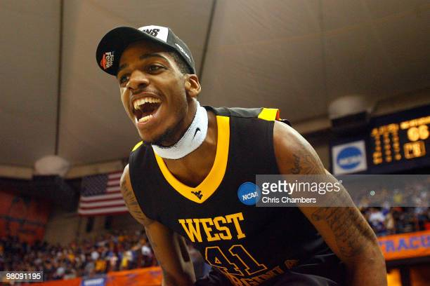 John Flowers of the West Virginia Mountaineers celebrates on the scorer's table after West Virginia won 73-66 against the Kentucky Wildcats during...