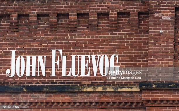 John Fluevog signage on an old brick wall in the Distillery District Designer shoe store name in white metal lettering