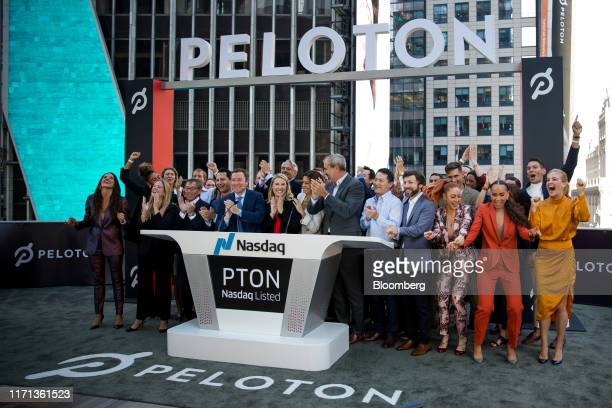 John Foley, co-founder and chief executive officer of Peloton Interactive Inc., center left, rings the opening bell during the company's initial...