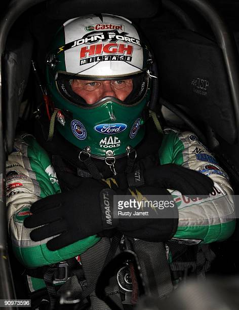 John Force driver of the Castrol GTX High Mileage Ford prepares to drive during qualifying for the NHRA Carolinas Nationals on September 19 2009 at...