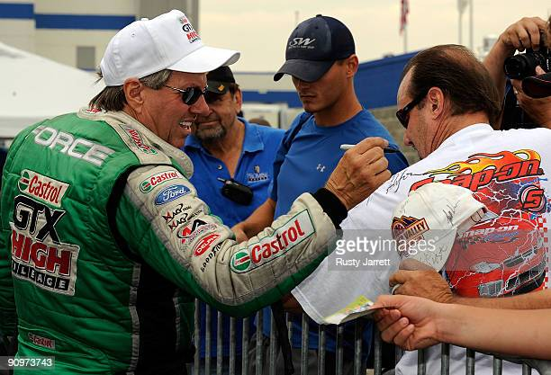 John Force driver of the Castrol GTX High Mileage Ford signs a fan's shirt during qualifying for the NHRA Carolinas Nationals on September 19 2009 at...