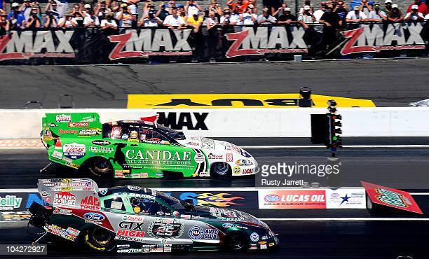 John Force driver of the Castrol GTX HM Funny Car races Paul Lee driver of the Jim Dunn/Canidae/Lucas Oil Funny Car during the O'Reilly Auto Parts...