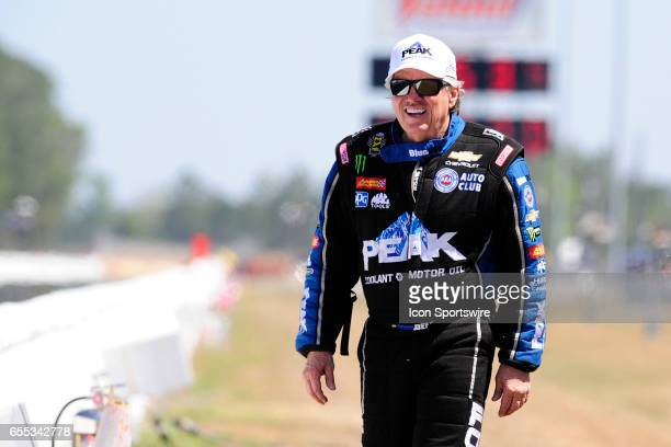 John Force JFR Chevrolet Camaro SS NHRA Funny Car driver stand near the retaining wall to watch daughter Brittany Force John Force Racing NHRA Top...