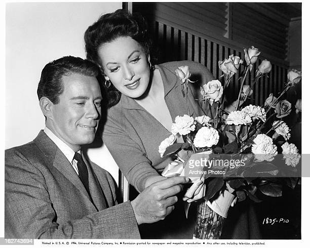 John Forsythe and Maureen O'Hara receive flowers on set of the film 'Everything But The Truth' 1956