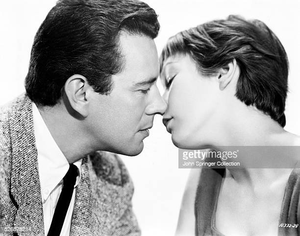 John Forsythe and Shirley MacLaine tilt their heads for a kiss for a promotional shot for the 1955 Alfred Hitchcock film The Trouble with Harry in...