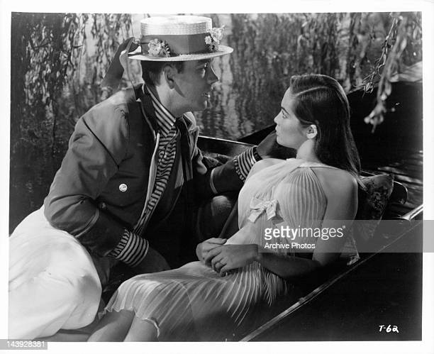 John Fraser laying next to Nancy Kwan on small boat in a scene from the film 'Tamahine' 1963