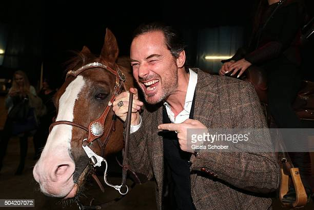 John Friedmann poses with a horse during the 'APASSIONATA Im Bann des Spiegels' VIP reception at Olympiahalle on January 9 2016 in Munich Germany