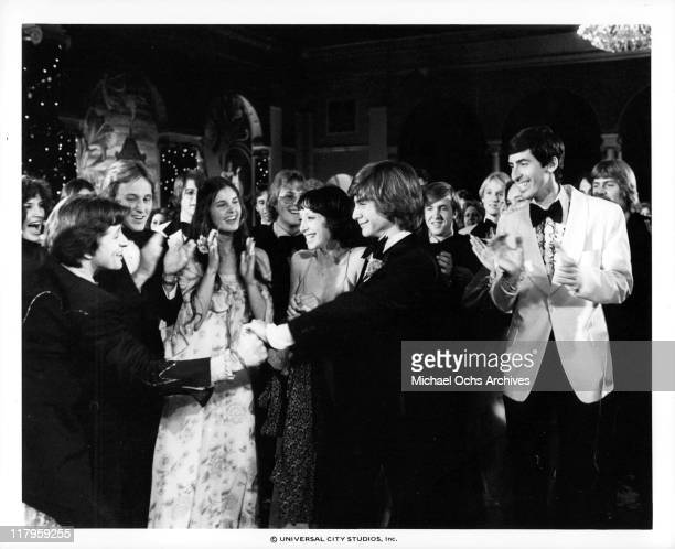 John Friedrich shaking hands with an extra while stadning with Didi Conn during a party in a scene from the film 'Almost Summer', 1978.