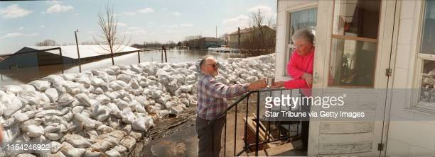 John Fritsche gets a cup of coffee from his mother Hilda Fritsche between checking water pumps and the sand bag dikes holding back the Minnesota...
