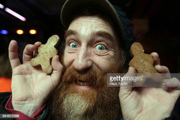 John Gallagher poses for a picture holding gingerbread men during the Ginger Pride festival in Belfast Northern Ireland on February 11 2017 The...