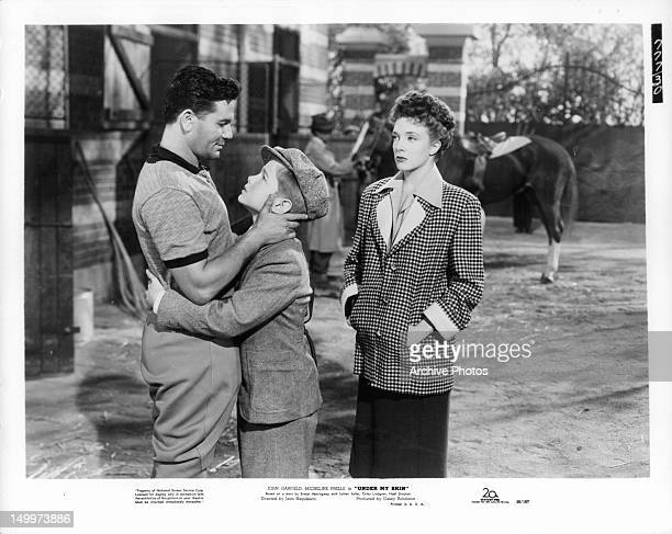 John Garfield holding son Orley Lindgren as Micheline Presle watches in a scene from the film 'Under My Skin' 1950
