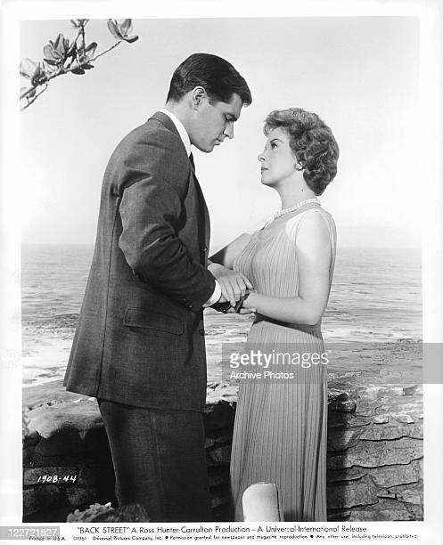 John Gavin and Susan Hayward standing face to face holding hands in a scene from the film 'Back Street' 1961