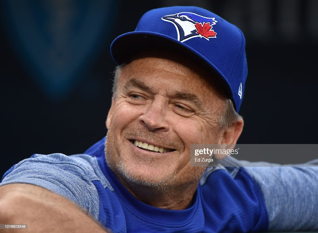 John Gibbons #5 manager of the Toronto Blue Jays looks on from the dugout as he waits for a game to begin agains the Kansas City Royals at Kauffman Stadium on August 14, 2018 in Kansas City, Missouri.