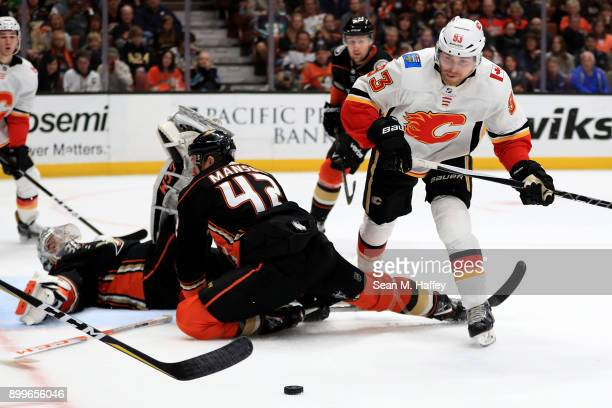 John Gibson and Josh Manson of the Anaheim Ducks defend atainst Sam Bennett of the Calgary Flames during the second period of a game at Honda Center...