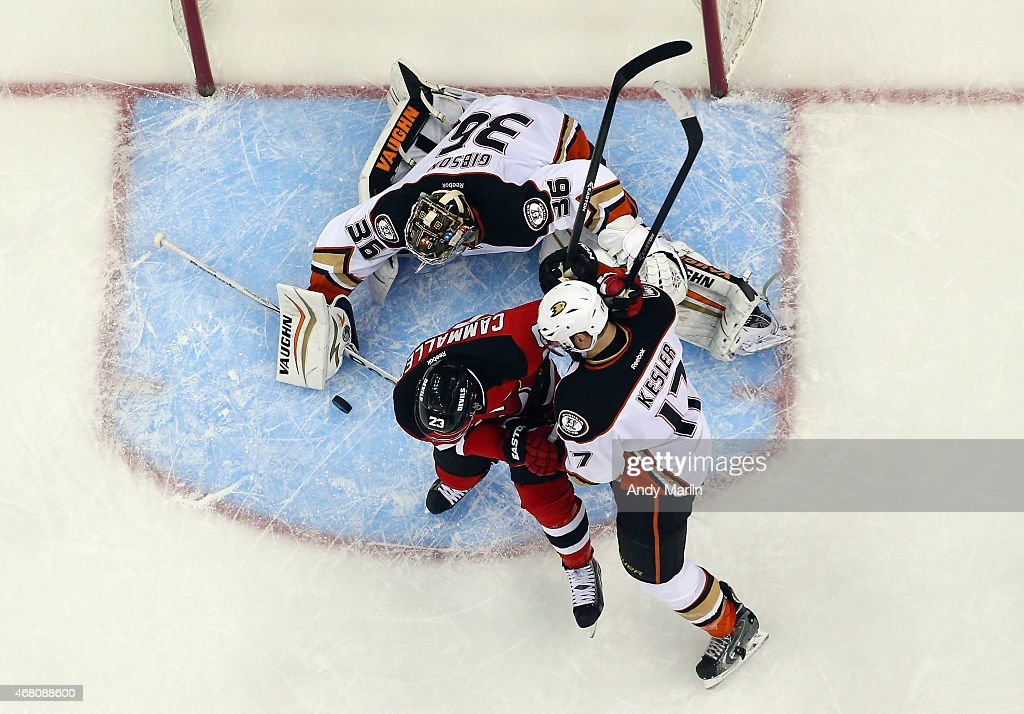 John Gibson #36 of the Anaheim Ducks makes a save as Ryan Kesler #17 checks Mike Cammalleri #23 of the New Jersey Devils during the game at the Prudential Center on March 29, 2015 in Newark, New Jersey.