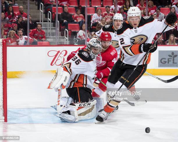 John Gibson of the Anaheim Ducks makes a save on Darren Helm of the Detroit Red Wings as Josh Manson of the Ducks skates after the loose puck during...