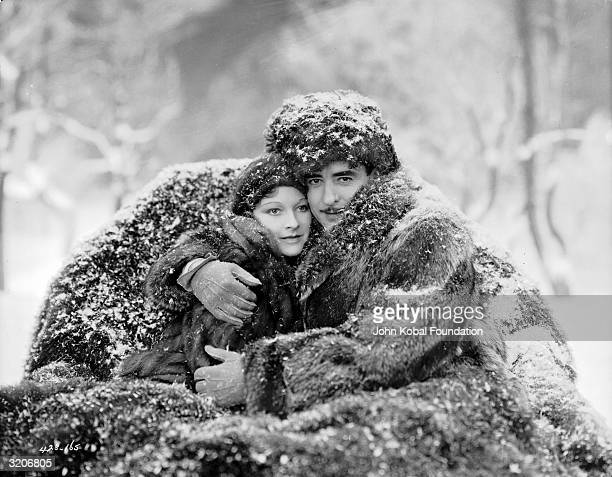 John Gilbert and Eleanor Boardman cuddle up together in the snow in a scene from Fred Niblo's 1930 film 'Redemption'