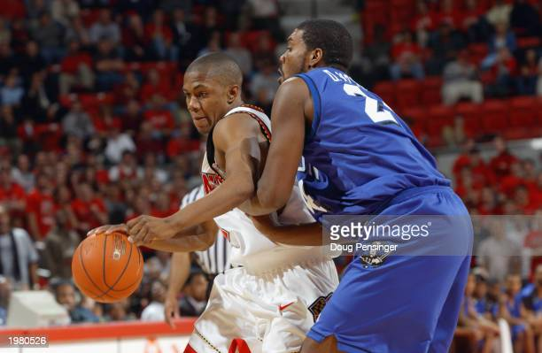 John Gilchrist of the Maryland Terrapins drives against Dwayne McNeal of the Hampton Pirates during the game at Comcast Center on January 8 2003 in...