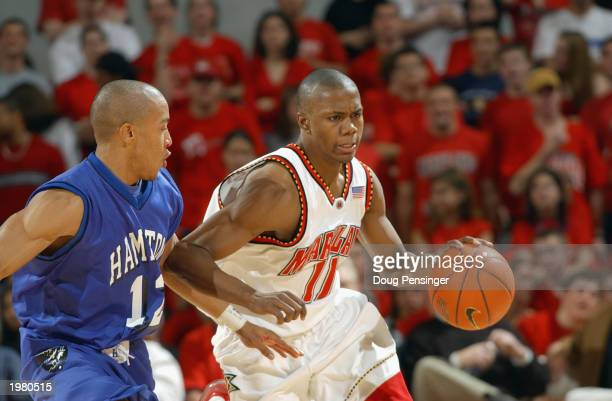 John Gilchrist of the Maryland Terrapins drives against Jamaal James of the Hampton Pirates during the game at Comcast Center on January 8 2003 in...