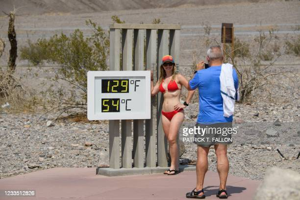 John Gillette takes a photo of Sarah Null as she stands in a swimsuit next to a thermometer displaying temperatures of 129 Degrees Fahrenheit at the...