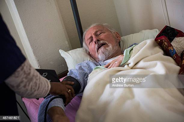 John Gillis age 73 a hospice care patient diagnosed with terminal colon cancer exhales while having his blood pressure checked by a nurse in the...