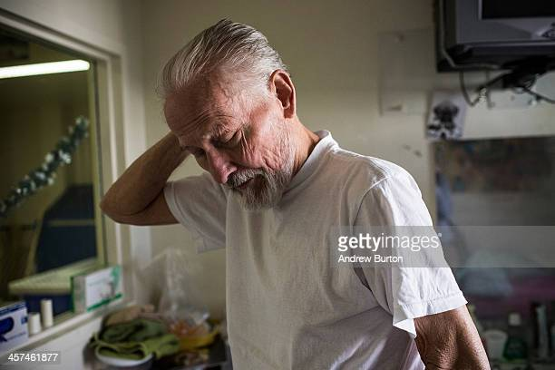 John Gillis age 73 a hospice care patient diagnosed with terminal colon cancer brushes his hair in the hospice care wing of California Medical...