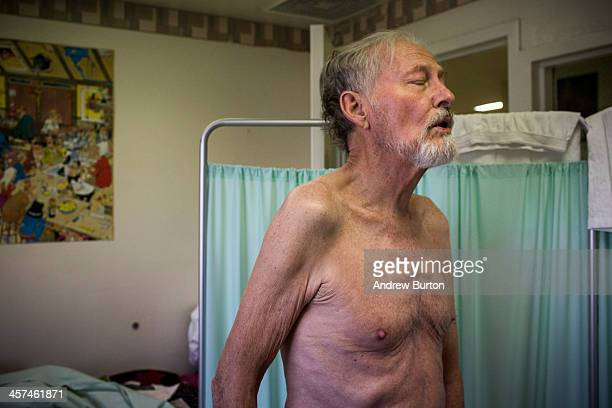John Gillis age 73 grimmaces while an open wound a development due to terminal colon cancer is treated by fellow prisoner and hospice care worker JP...