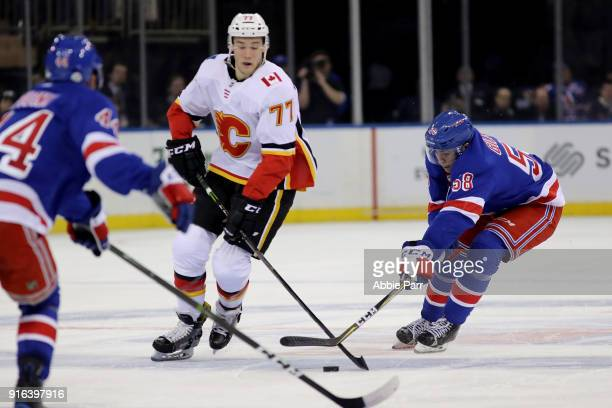 John Gilmour of the New York Rangers fights for the puck in his first NHL game against Mark Jankowski of the Calgary Flames during their game at...