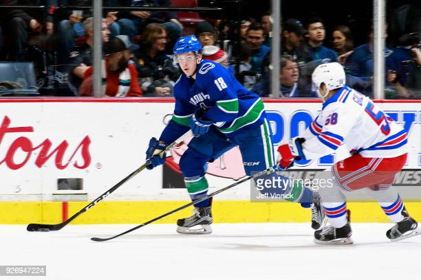 John Gilmour of the New York Rangers looks on as Jake Virtanen of the Vancouver Canucks skates up ice with the puck during their NHL game at Rogers...