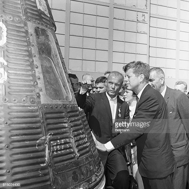 John Glenn shows President Kennedy the Friendship 7 the space capsule which carried Glenn around the world three times in orbit Glenn is wearing the...