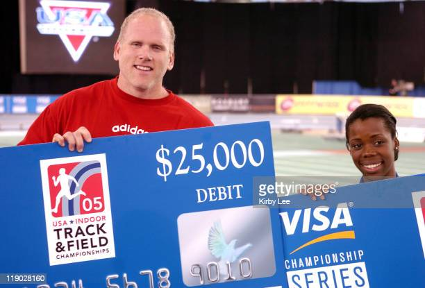 John Godina and Angela Daigle hold $25,000 checks after winning the men's and women's title of the inaugural VISA Championship Series in the USA...