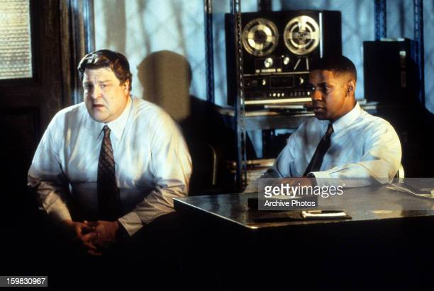 John Goodman and Denzel Washington sitting in dark room in a scene from the film 'Fallen' 1998