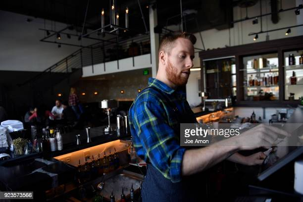 John Gregory bartender entering drink orders into the point of sale system at Julep Restaurant Denver serving a sophisticated southern style menu and...