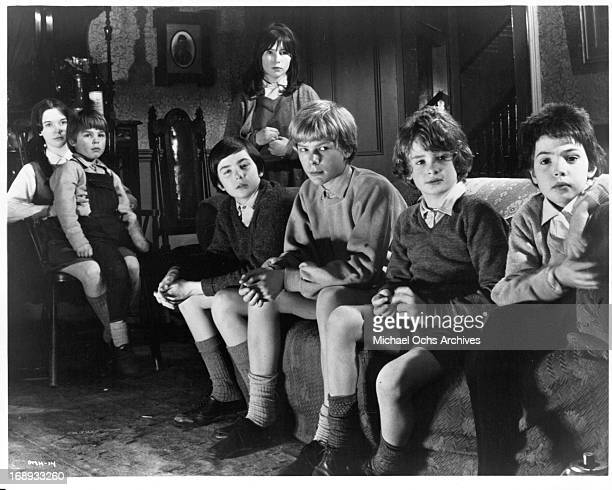 John Gugolka Louis Sheldon Williams Gustav Henry Margaret Brooks Mark Lester and Phoebe Nicholls and Pamela Franklin are all seated and staring in...