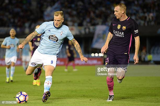 John Guidetti of RC Celta de Vigo competes for the ball with Mathieu of FC Barcelona during the La Liga match between Real Club Celta de Vigo and...