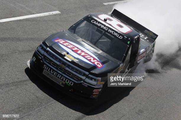 John H Nemechek driver of the Fleetwing Chevrolet celebrates with a burnout after winning the weather delayed NASCAR Camping World Truck Series Alpha...