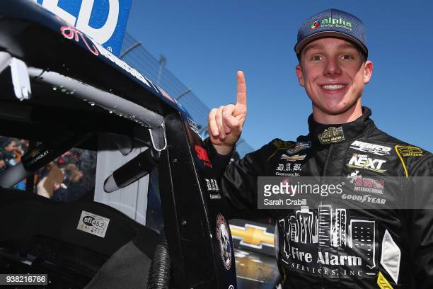 John H Nemechek driver of the Fleetwing Chevrolet poses with the winner's decal on his truck in Victory Lane after winning the weather delayed NASCAR...