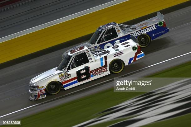 John H Nemechek driver of the NEMCO Motorsports Chevrolet leads Johnny Sauter driver of the Allegiant Airlines Chevrolet during the NASCAR Camping...
