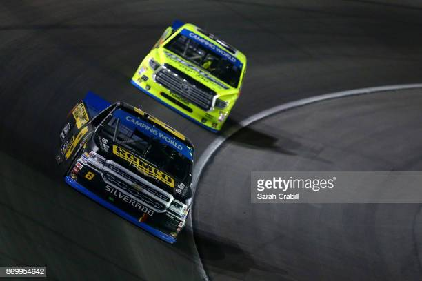 John H Nemechek driver of the ROMCO Equipment/Fire Alarm Services Chevrolet leads Matt Crafton driver of the Ideal Door/Menards Toyota during the...